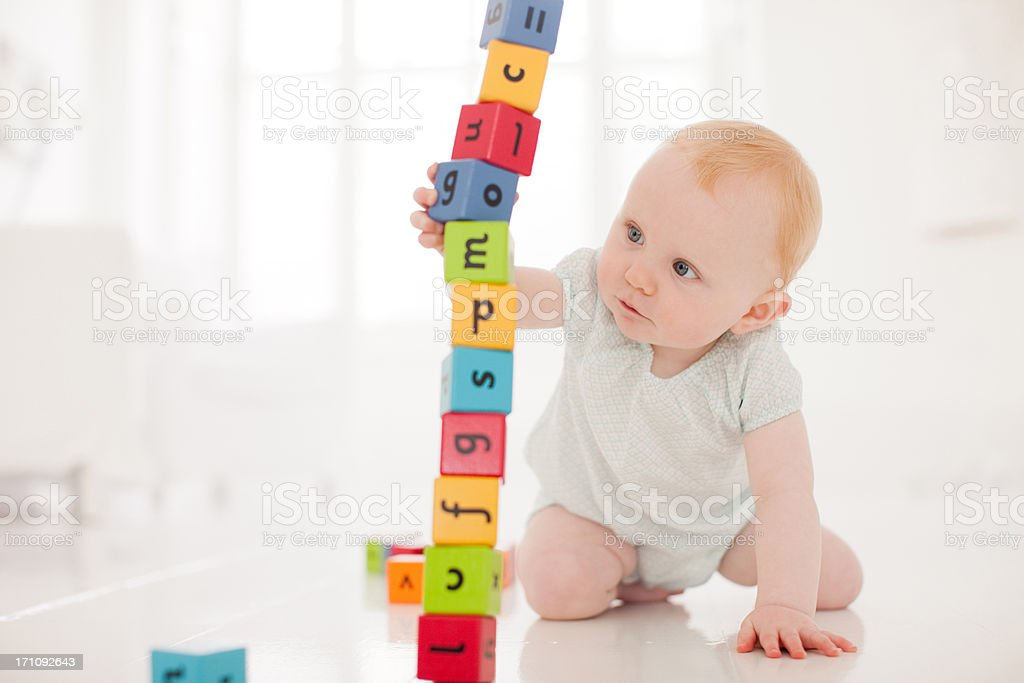 Baby on floor pulling wood block from middle of stack stock photo