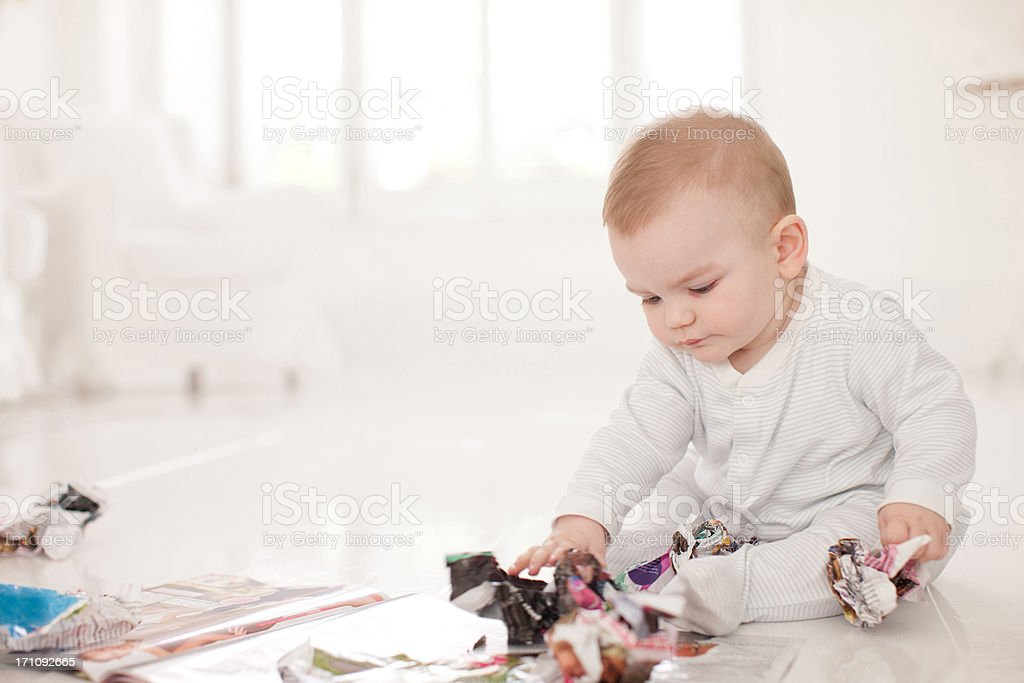 Baby on floor with crumpled paper