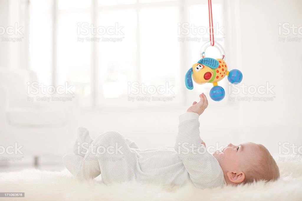 Baby on rug reaching for hanging toy overhead stock photo