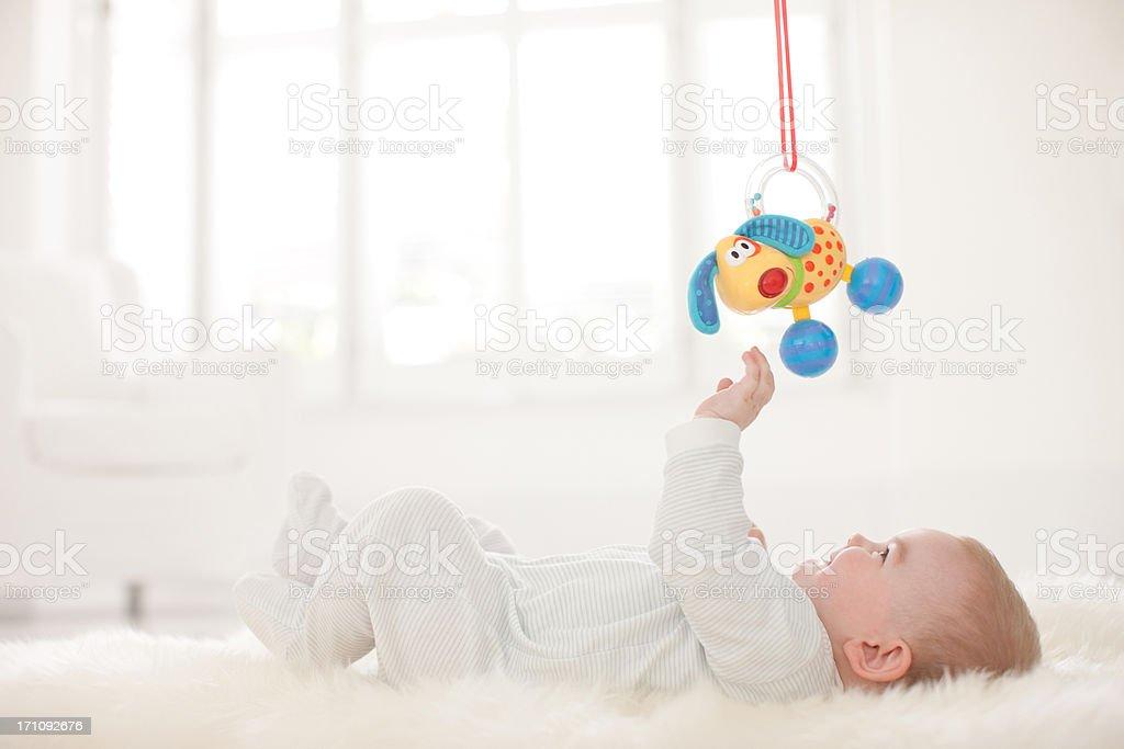 Baby auf Teppich greifen zum Aufhängen Spielzeug über – Foto