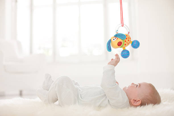 Baby on rug reaching for hanging toy overhead圖像檔