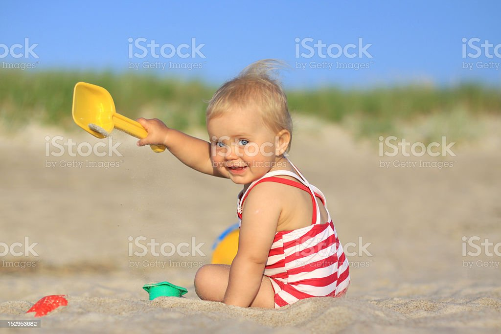 Baby on the beach with yellow shovel royalty-free stock photo