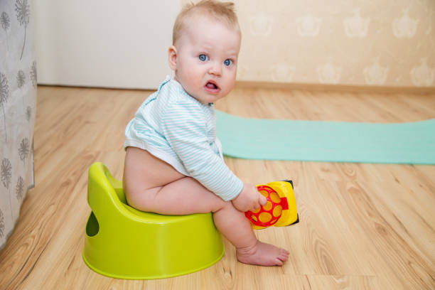 Baby on the potty. The child of the first year of life sitting on a potty in the room. Baby on the potty. The child of the first year of life sitting on a potty in the room. poop stock pictures, royalty-free photos & images