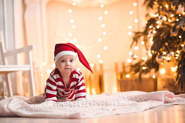 baby over christmas lights - festliche babymode junge stock-fotos und bilder