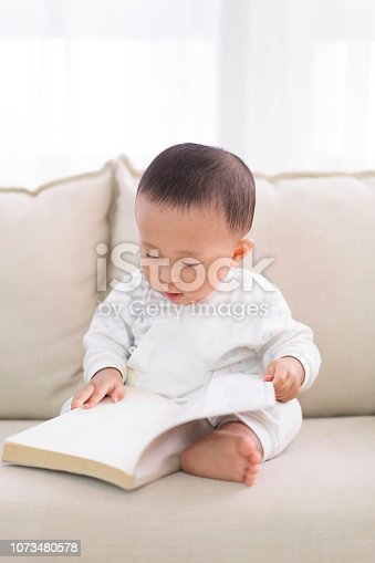Reading baby, Sitting on the sofa at home.