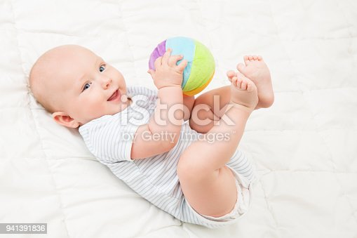 istock Baby Play Toy Ball, Happy Kid Lying on Back Playing Soft Toys, Infant Child on White Blanket 941391836