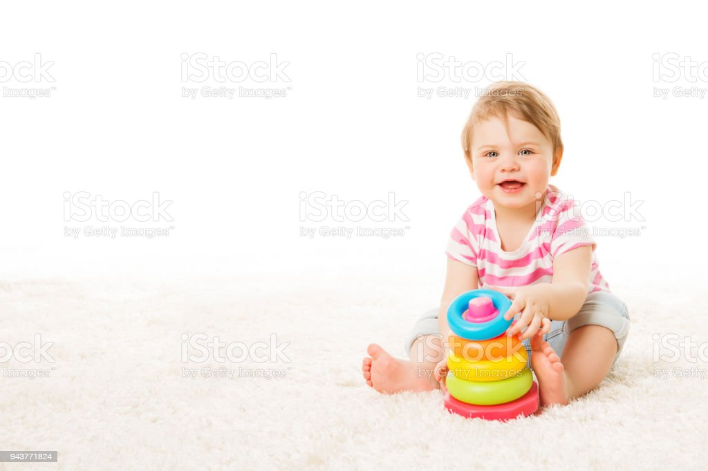 Baby Play Toy Rings Pyramid, Infant Kid Playing Building Blocks, one year Child Sitting on Carpet stock photo