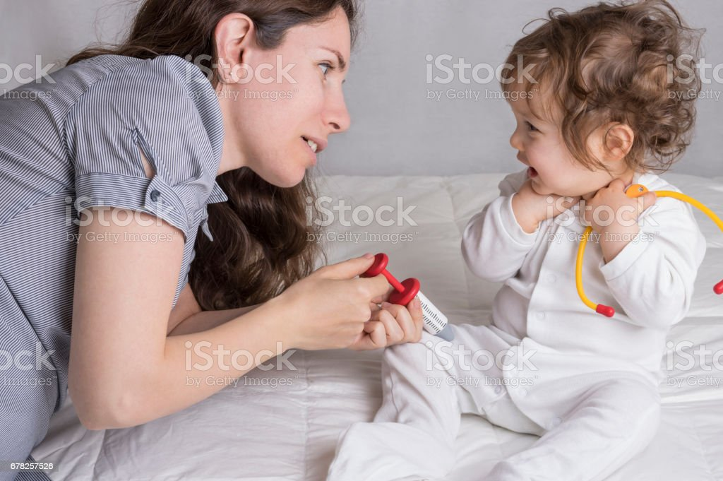 Baby playing a doctor with mother stock photo