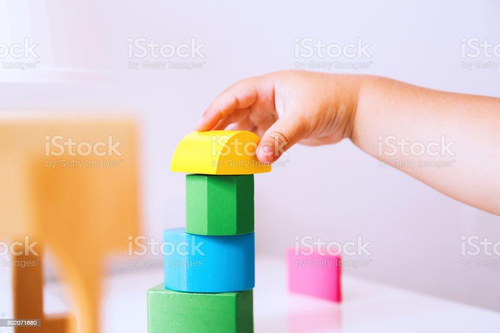 Baby speelt en ontdekking met kleurrijke speelgoed thuis, close-up detail. foto