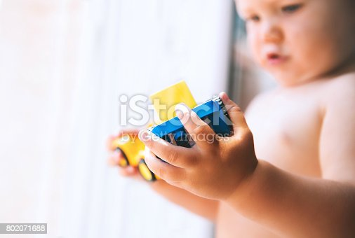 istock Baby playing and discovery with colorful toys at home, close-up detail. 802071688