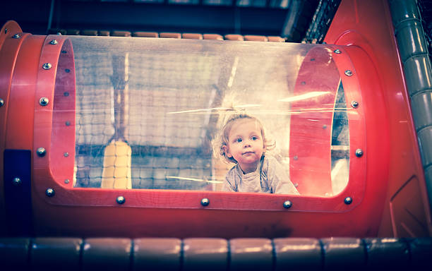 Baby playing inside a toy tunnel stock photo