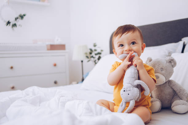 Bebé jugando en la cama - foto de stock