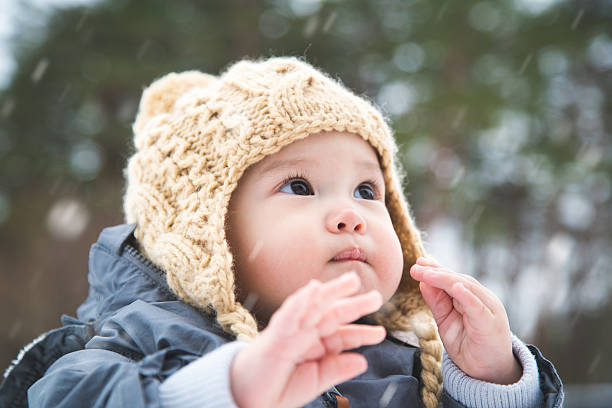 Baby playing outside in the snow stock photo