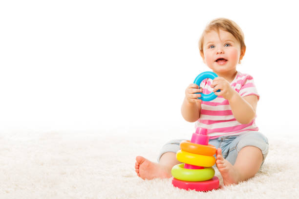 Baby Playing Toy Rings, Infant Child with Colorful Circle Pyramid, Happy Kid on Carpet stock photo