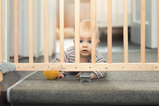 baby playing with ball behind safety gates stock photo