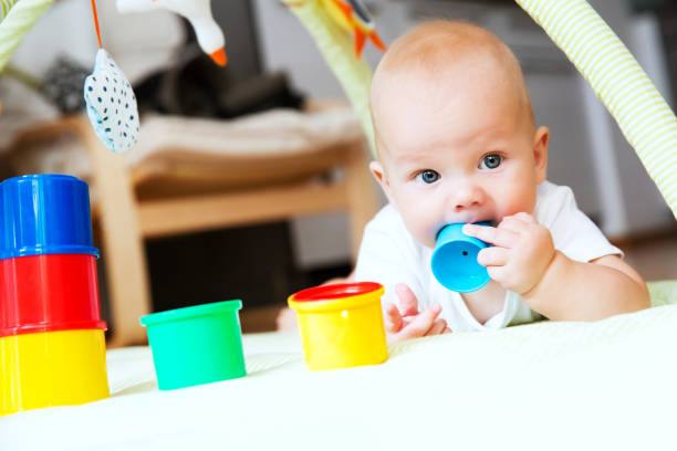 Baby playing with colorful toys at home. stock photo