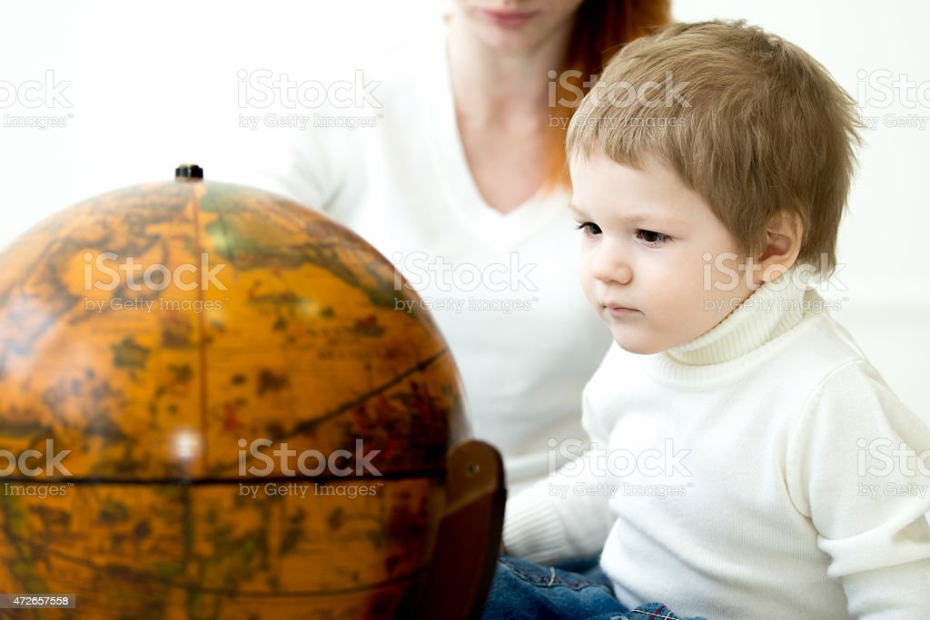 Baby playing with earths globe stock photo