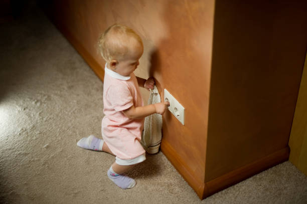 Bebé jugando con toma de corriente en el suelo en casa - foto de stock