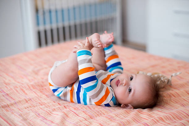 Baby playing with his feet stock photo