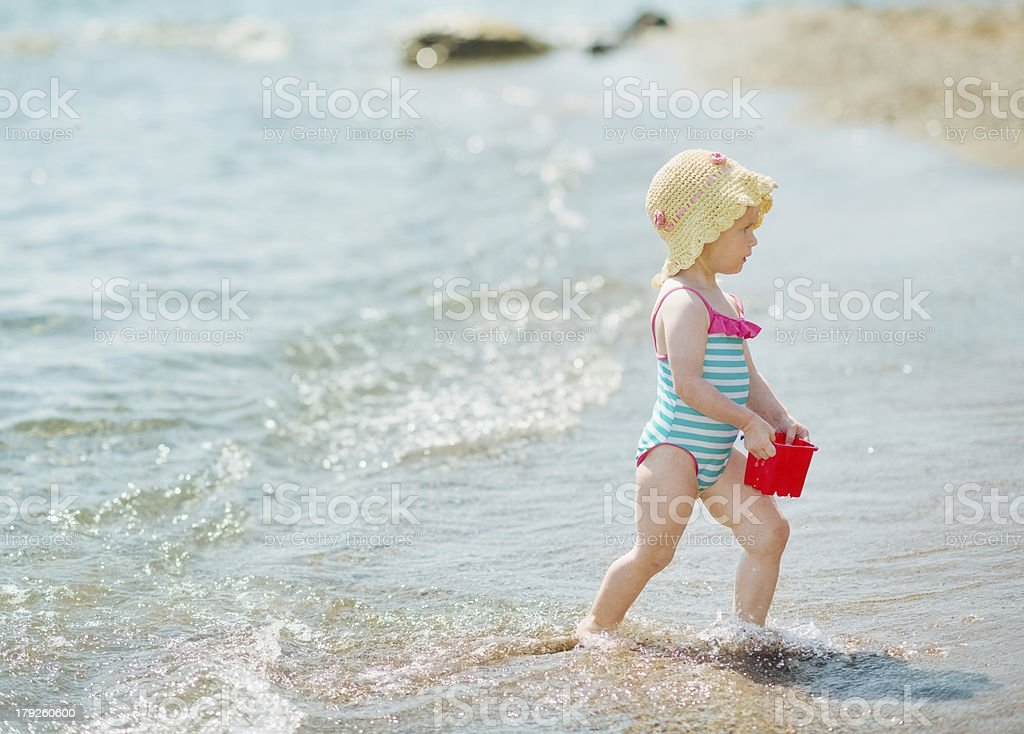 Baby playing with pail on seashore royalty-free stock photo
