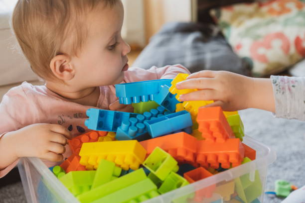 Baby playing with toy blocks. Kindergarten concept. baby playing in the box with toys. Education and play in the kindergarten. Nursery children playing with the teacher. cute little girl playing toys. girl playing plastic wooden toys at home. stock photo