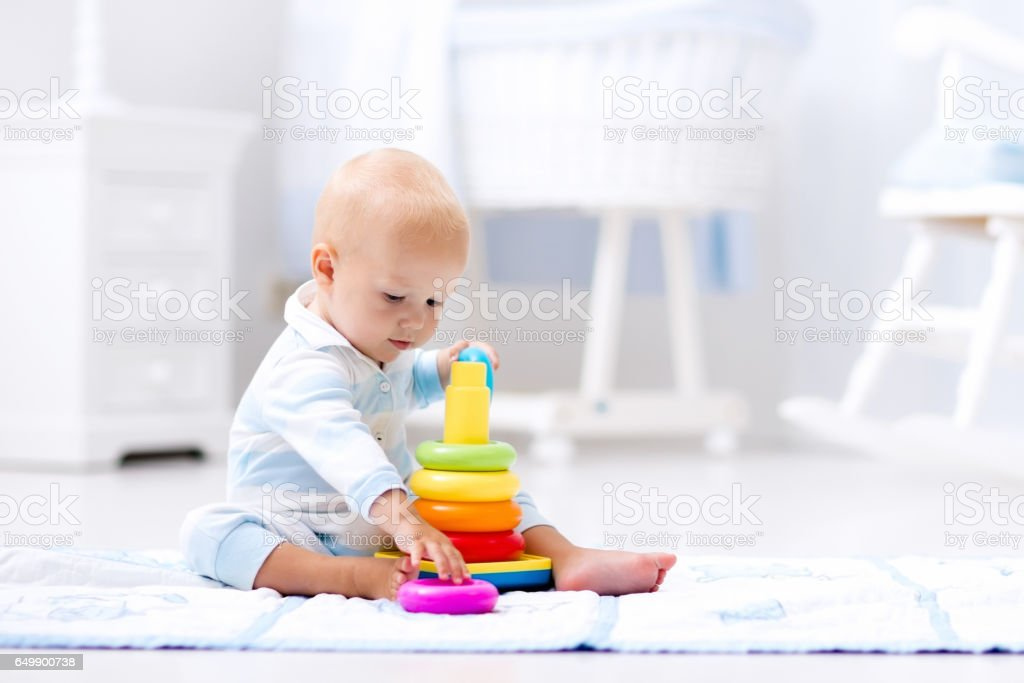 Baby playing with toy pyramid. Kids play stock photo