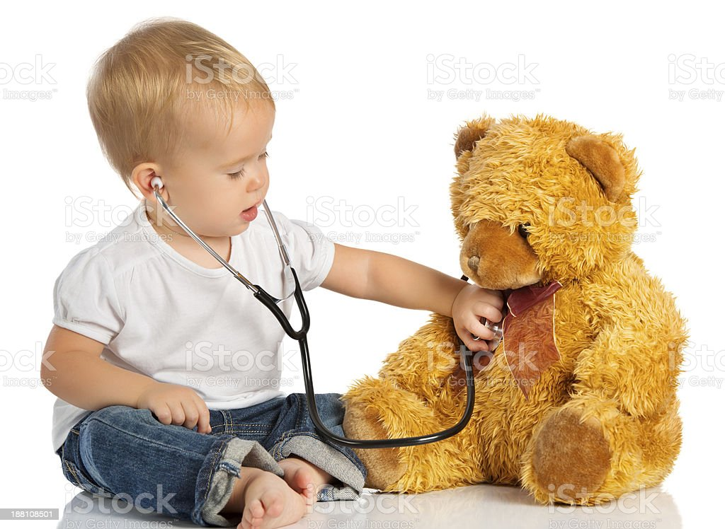 baby plays in doctor toy bear and stethoscope stock photo