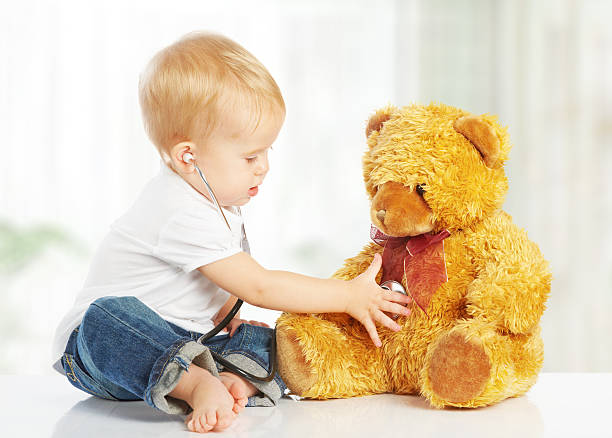 baby plays in doctor toy teddy bear and stethoscope stock photo