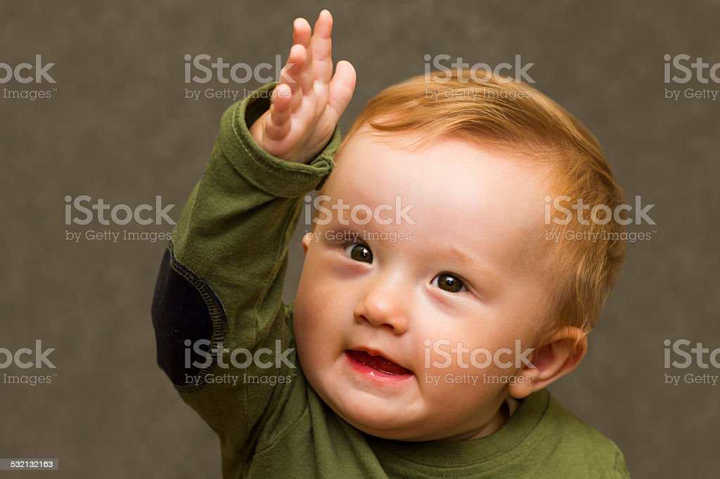 Baby pointing forward with his hand stock photo