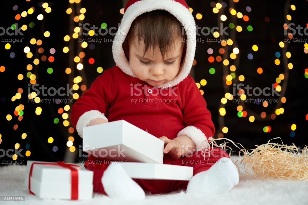 baby portrait in christmas decoration, dressed as Santa, boke lights on dark background, winter holiday concept photo libre de droits