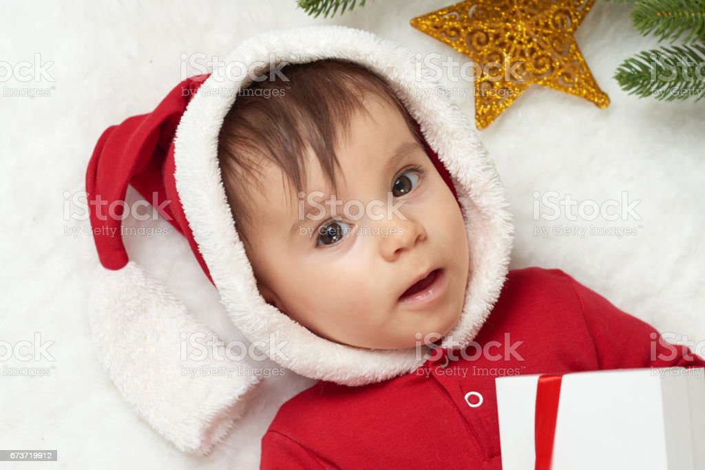 baby portrait in christmas decoration, dressed as Santa, lie on fur near fir tree and play with gifts, winter holiday concept photo libre de droits