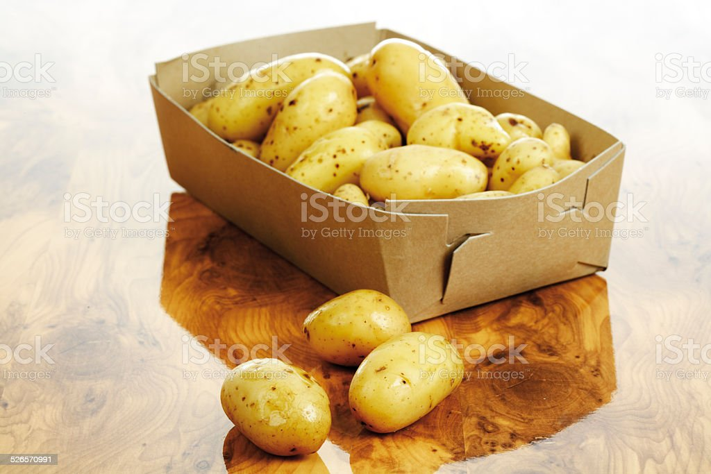 Baby potatoes in cardboard stock photo