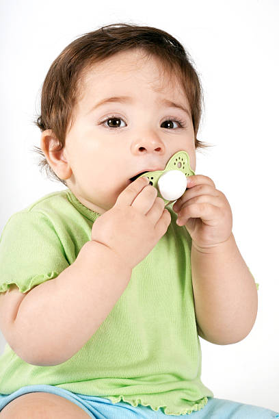 Baby putting a dummy into mouth Young baby putting a pacifier into her mouth. ventriloquist's dummy stock pictures, royalty-free photos & images