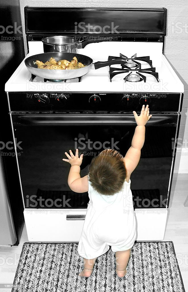 Baby Reaching for Stove stock photo