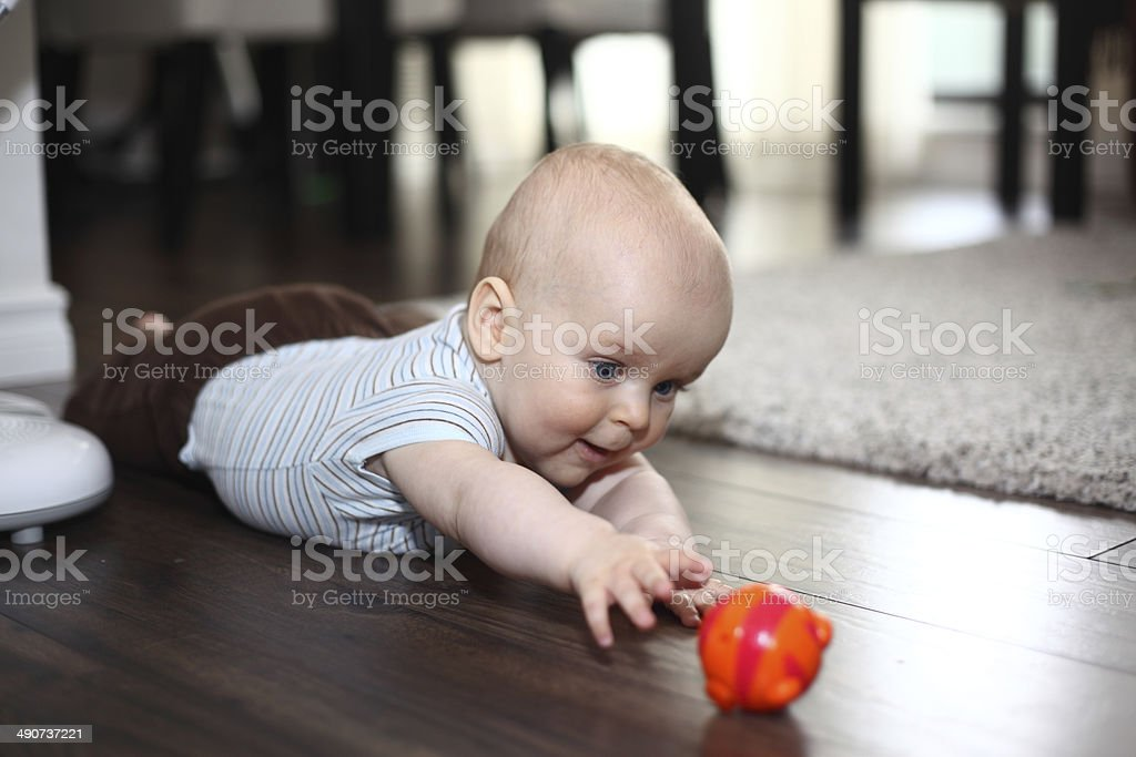 Baby reaching for the toy stock photo