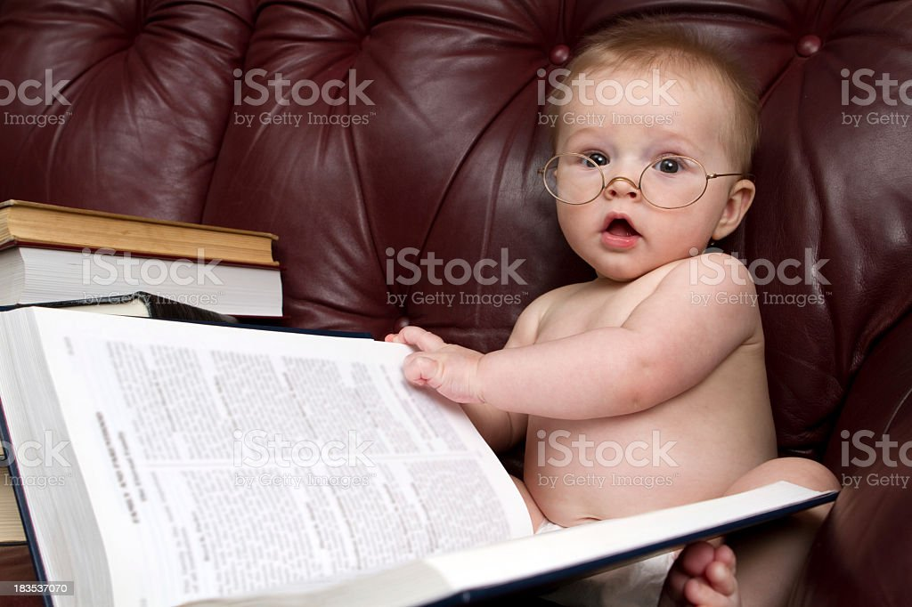 Baby reading a giant book while wearing glasses royalty-free stock photo