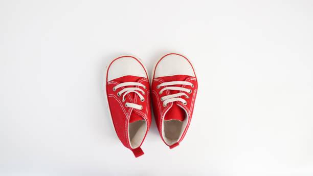 baby rote sneakers isoliert auf weißem hintergrund. babyschuhe - babyschuh stock-fotos und bilder