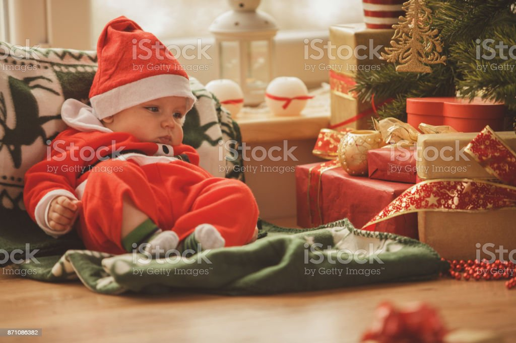 Baby resting at Christmas tree stock photo