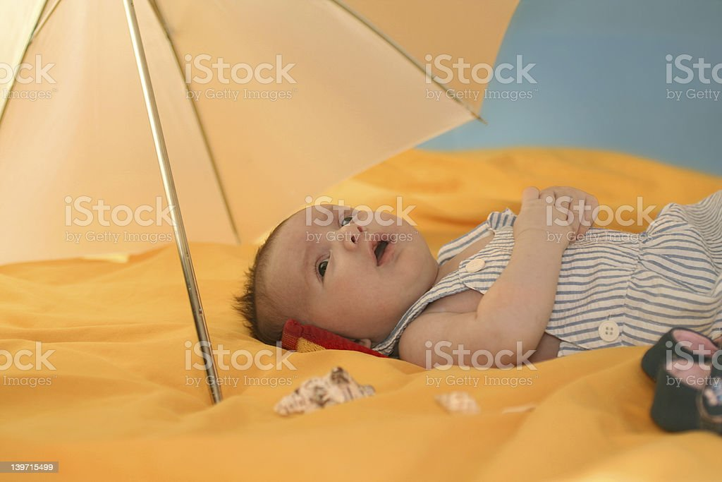 baby resting uner umbrella stock photo