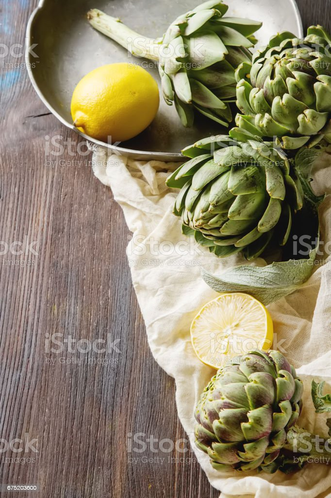 Baby ripping organic Artichokes in the rustic wooden board with lemon, solfetka. Dark background. royalty-free stock photo