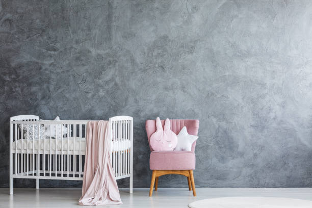 Baby room with crib and armchair stock photo