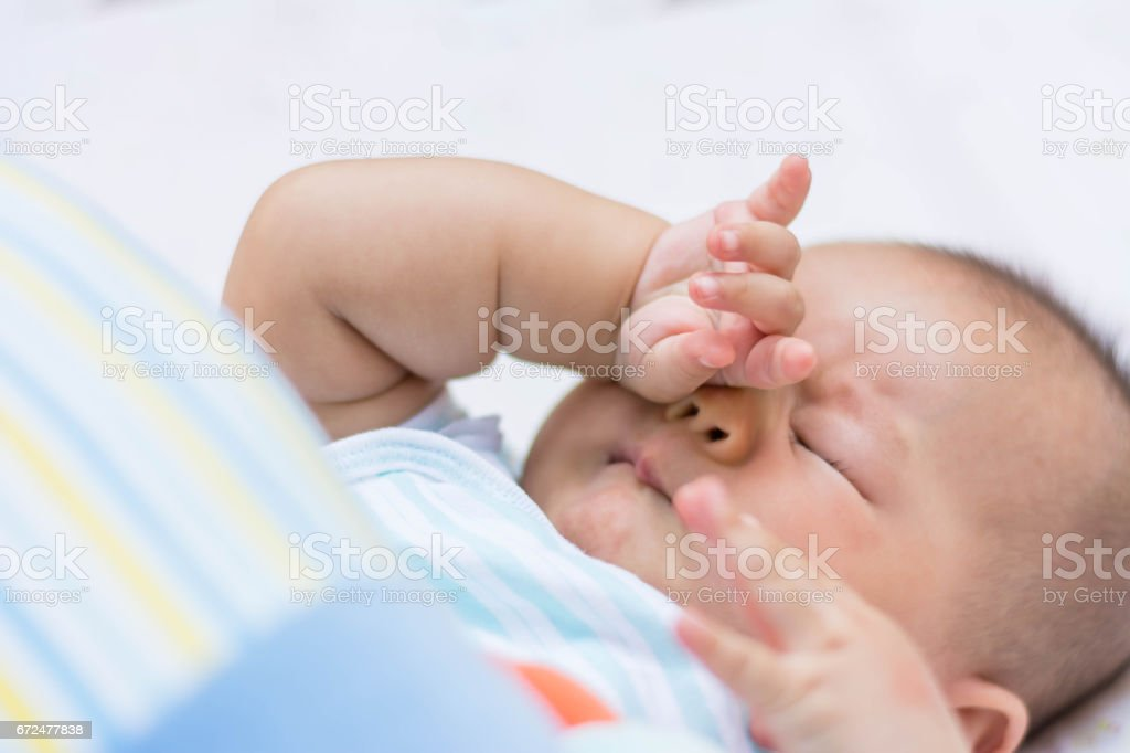 Baby rubbing it's eyes, stock photo