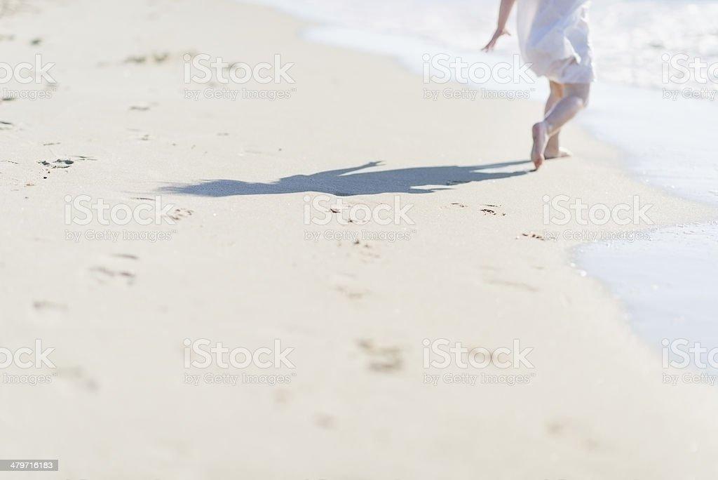 Baby running on sea shore. Closeup stock photo