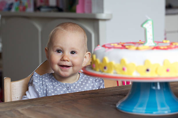 Baby sat at table with birthday cake and number one candle First birthday, 1 year old baby girl. first birthday stock pictures, royalty-free photos & images
