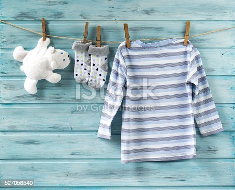 istock Baby shirt, socks and white toy bear on a clothesline 527056540