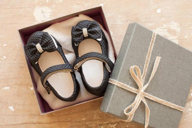 babyschuh in geschenkbox auf holzhintergrund - geschenk zur taufe stock-fotos und bilder