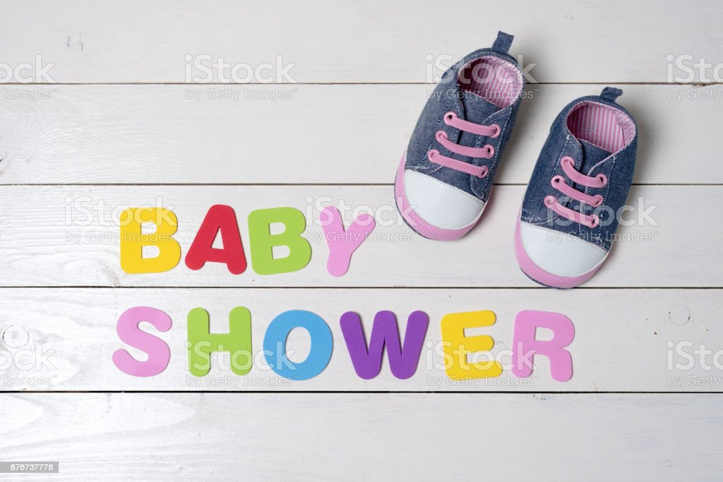 Baby shoes on white wooden table. stock photo