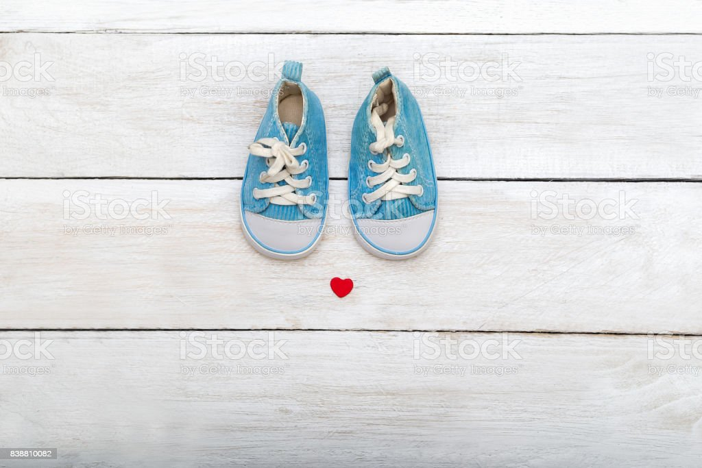 Baby shoes on wooden background. flat lay stock photo