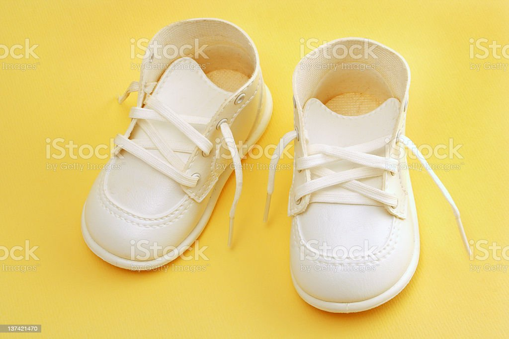 baby shoes over yellow stock photo