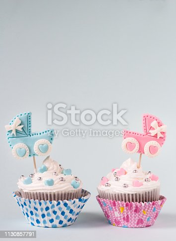 886700726istockphoto Baby shower cupcake for a girl and a boy. Newborn announcement concept. Text space 1130857791